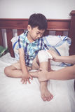 Crying child injured. Mother bandaging son`s knee.  Vintage tone. Crying child injured. Mother bandaging son`s knee on bed inside bedroom, bandage in focus Stock Photo