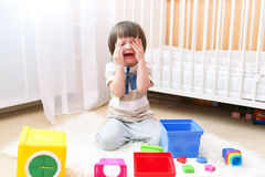 Crying child scatters toys at home. Crying little boy scatters toys at home Royalty Free Stock Images