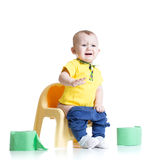 Crying child sitting on chamber pot with toilet. Paper rolls stock photography