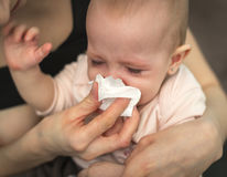 Crying child,. A small, sick, crying child, whom the mother wipes with a paper towel Royalty Free Stock Images