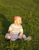 Crying child. The small child who sits on a grass and cries Royalty Free Stock Photography