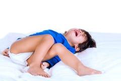Crying disabled toddler boy lying on white mat Royalty Free Stock Image