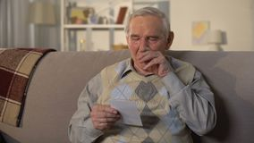 Crying elderly man looking at photo, remembering old lost friend, memories. Stock footage stock video