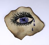 Crying Eye. A teary eye with long eyelashes on a burnt piece of paper with a white background Stock Images