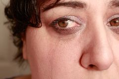 Crying eyes  of woman. Close up view of ethnic woman with short hair showing crying expression Stock Photo