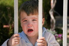 Crying or freedom. Little boy crying behind the gate stock images