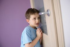 Crying, frightened child listening to a parent talking through the door. With a glass pressed to his ear stock photography