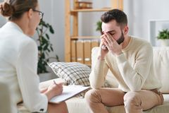 Crying in front of counselor. Crying young patient of psychotherapist sitting on couch in front of the women during individual session stock photography