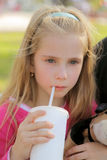 Upset girl drinking. A little girl very upset and crying drinking from a cup with a straw royalty free stock images