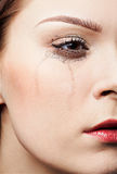 Crying girl. Close-up portrait of beautiful crying girl with smeared mascara Stock Image
