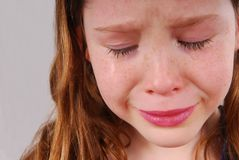 Crying Girl. Young girl crying with tears flowing down freckled cheeks Royalty Free Stock Photos