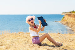 Crying girl on the beach with laptop Royalty Free Stock Photography