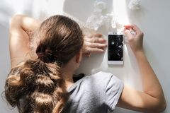 Crying girl with broken smart phone. Crying curly hair girl with broken smart phone royalty free stock images