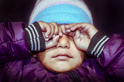 Crying girl child. Crying or weeping girl child wearing woolen cap and jaket portrait Royalty Free Stock Photo