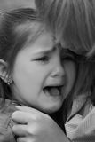 Crying girl close-up conforted. By mother, black and white royalty free stock images