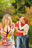 Crying girl and a couple. Crying girl and kissing couple on a background Royalty Free Stock Image