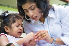 Crying girl with injured finger. Indian family outdoor. Mother is comforting her crying daughter with injured finger Royalty Free Stock Images