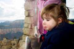 Crying Girl Looks Out Window at Grand Canyon. A sad little girl with a single tear streaming down her cheek looks out the big picture window at the Grand Canyon Royalty Free Stock Images