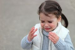 crying girl with pigtails in a sweater and vest raises her hands up stock image