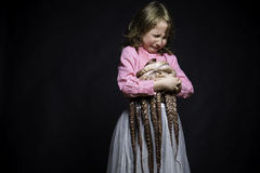 Crying girl in a pink blouse and white skirt on black textured background with octopus  Royalty Free Stock Images