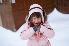 Crying girl in the pink jacket gently freezing outside in winter Stock Images