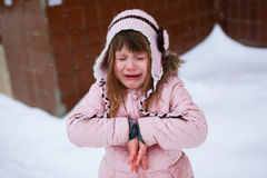 Crying girl in the pink jacket gently freezing outside in winter Royalty Free Stock Photography