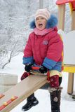 Shouting girll sitting on seesaw. Crying girl sitting on seesaw in winter park Stock Image