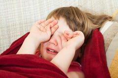 Crying girl on sofa Stock Photos