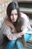 Crying girl on stairs. Crying girl with tears sitting on wooden stairs near red brick wall Stock Photos
