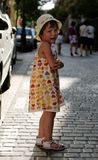 Crying girl on street. Crying young girl standing on a stone pavement along a street Stock Image