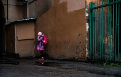Crying girl in vibrant clothes near the blind wall. In the dark backyard royalty free stock image