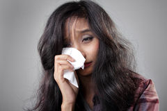 Crying girl wipes her tears stock images