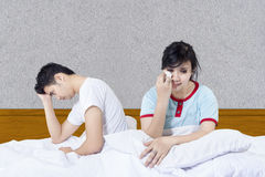 Crying girlfriend after fight in bed. On grey background royalty free stock photos
