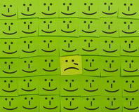 Crying and happy concept. Background of Sticky Notes. Crying and happy concept. Background of green sticky notes. Crying sticky note is among happy sticky notes stock photo