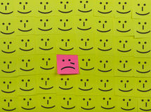Crying and happy concept. Background of Sticky Notes. Crying and happy concept. Background of green sticky notes. Crying sticky note is among happy sticky notes royalty free stock photography