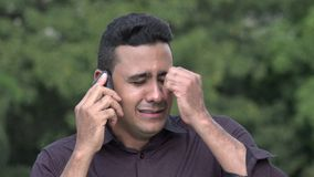 Crying Hispanic Man Using Cell Phone. A handsome adult hispanic man stock video footage