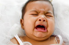 Crying Indian baby girl. Lying on bed Stock Photo