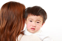 Crying Japanese little boy who is being held by her mother Stock Photos