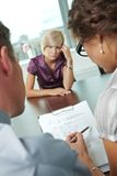 Crying during job interview. Woman applicant having failed job interview. Over the shoulder view. Focus placed on sheet in front all results are bad royalty free stock images