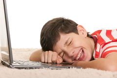 Crying with joy. A handsome lying on the white carpet boy is crying with joy after computer game; isolated on the white background Stock Photo