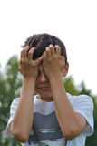 Crying kid, two hands to forehead. A young kid is crying, holding two hands to his forehead Royalty Free Stock Photography