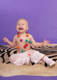 Crying little baby girl. On artificial zebra skin at the studio on the floor Royalty Free Stock Images