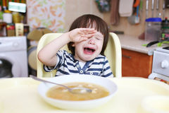 Crying little boy dont want to eat pea soup at home Royalty Free Stock Images