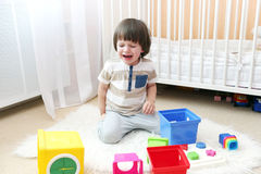 Crying little boy scatters toys Royalty Free Stock Photo
