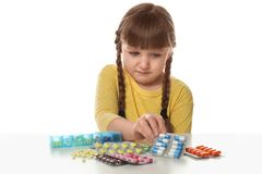 Crying little child with many different pills. Danger of medicament intoxication. Crying little child with many different pills on white background. Danger of stock photo
