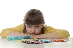 Crying little child with many different pills on white. Danger of medicament intoxication. Crying little child with many different pills on white background stock photo