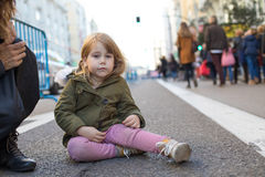 Crying little child sitting on asphalt street Stock Images