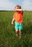 Crying little girl. Little crying girl in an orange t-shirt in the meadow Stock Image