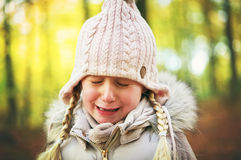 A crying little girl in autumn forrest Stock Images
