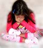 Crying little girl with bunny slippers. Stock Images